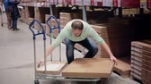 checagem : A man is taking a box from the shelf, putting it on the trolley, checking his list in a storage warehouse Stock Footage