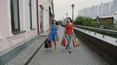 shopping bag sale : Happy young women friends walking with shopping bags, talking discuss having fun. slow mo stedicam shot