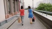 bohatý : Two beautiful young woman friends walking with shopping bags, talking having fun, back view, slow mo stedicam shot Dostupné videozáznamy