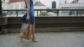 bohatý : legs slender young woman, walking in the city down the street with shopping bags, side view, slow mo, stedicam shot
