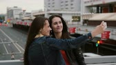 cabelos claros : Two girls best friends taking selfie, standing on the city bridge, talking, smiling, laughing. 4K