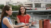ресторан : Two beautiful women drinking coffee communicate in a cafe, talking after shopping. 4k