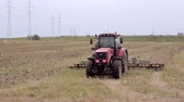 rolnik : An agricultural tractor, plowing a field for sowing, moving to the camera. Birds are flying around