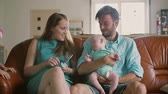 family values : Family of four is sitting on the sofa: father holding his newborn son and daughter jumps with joy near them. Slow mo Stock Footage