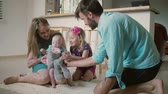 contraste : Young beautiful family is playing with the youngest baby son on the kitchen floor. Slow motion Stock Footage