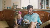 family values : blond little girl is choosing a story that her loving father will read on the sofa. Slow motion Stock Footage