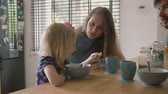 kitchen counter : Beautiful young mother and her cute blond daughter are laughing happily at kitchen table. Slow mo Stock Footage