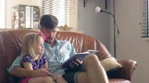 para cima : A young father and his happy little blond daughter are reading a story on leather sofa in the dining room. 4K