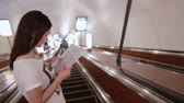 escada rolante : Pretty girl in subway. Young woman with long dark hair looking at a map on an escalator going up.