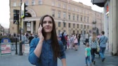 Боке : Busy street in the city centre. Beautiful brunette lady in denim smiling, talking on the phone. Slow mo, steadicam shot