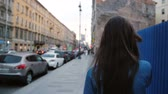 получать : Backview of young woman walking along a blue fence, talking on the phone. Lady walks in the city. Slow mo steadicam shot