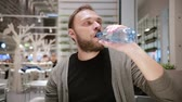 sedento : Drinking water. Handsome man with a beard opening a bottle of water sitting in a public place. Man is thirsty.