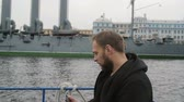 крейсер : Happy handsome man has great time sightseeing. Taking selfie in front of Cruiser Aurora, uses his smartphone, slow mo