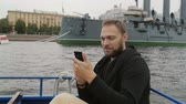 utilização : Happy handsome man sightseeing in St Petersburg. Taking selfie in front of Cruiser Aurora, uses his smartphone, slow mo