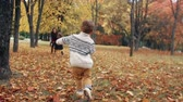 atender : happy cute brother and sister a little boy and girl runs to his mother through amazing autumn alley in the park slow mo Stock Footage