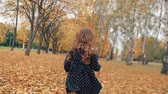 um : happy cute little girl with curly hair, in dress with polka dots runing through the autumn alley in the park slow mo
