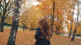 вид : back view cute little girl with curly hair, in dress with polka dots runing through the autumn alley in the park slow mo Стоковые видеозаписи