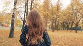 mosolyogva : happy cute little girl with curly hair, in dress with polka dots runing through the autumn alley in the park slow mo