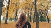 movement : back view happy cute little girl with curly hair runing through the autumn alley in the park slow mo Stock Footage