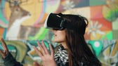 mosolyogva : woman uses a virtual reality glasses on a bright background 4k