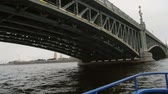 rio : Going from underneath the Trinity Bridge, St Petersburg, Russia. City landscape, the Peter and Paul Fortress, slow mo