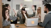 experiência : first experience with virtual reality glasses young team supports young beautiful brunette girl in modern startup office