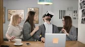 augmented reality : handsome man tries app for VR helmet virtual reality glasses his friends and colleagues supporting him in modern office