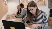 udržitelného : Young attractive girl is using a laptop, working with documents, making notes in the modern startup office