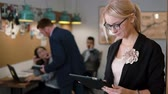 utilização : beautiful blonde business woman uses a tablet in the modern startup office team in the workplace Slow mo, steadicam shot Stock Footage