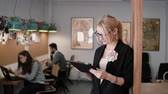utilização : 4k. young beautiful blonde businesswoman uses a touchscreen tablet in the modern startup office.