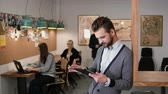 мотивированы : young handsome bearded man uses touchscreen tablet in the modern startup office.
