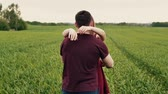 освещенный : Romantic young couple. They hug and spin around in a green field. Slow mo, steadicam shot Стоковые видеозаписи