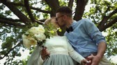 coroa : Bottom view. Young beautiful newlyweds kiss against a background of green tree in the park Stock Footage