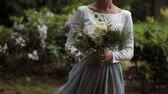 darbe : Close-up of hands young stylish bride with a beautiful bouquet of flowers in the park Stok Video
