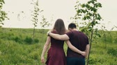 contraste : Backview of a loving couple walking in a garden. Hugging lovers enjoy nature Slow mo, steadicam shot Stock Footage