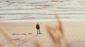 russo : A distant view of a guy who is writing Julia in Russian with his foot on the sand of a beautiful beach