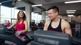 desportivo : Athletic man and woman walking on treadmills, talking and smiling. Work out in a sport club. Healthy lifestyle