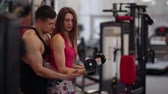instrutor : Sporty woman lifts dumbbells while working out in sport club. Athletic man is helping her to do the exercise correctly. Stock Footage