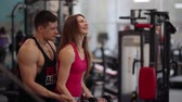 instrutor : Sporty woman lifts dumbbells while working out in the gym. She is trying hard while exercising. Man helps her. Stock Footage