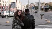 conservação : Back view of happy lovers walking in the street. Beautiful girl looks back into camera smiling. Slow mo, steadicam shot