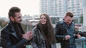 lotado : Two handsome young men and a beautiful girl talk and smile standing on the bridge in the city. Steadicam shot, slow mo