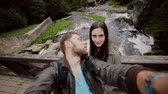 família : A beautiful young couple shares a cute kiss before taking a selfie on a wooden bridge over a waterfall. Vídeos