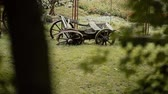 sáně : A behind-the-tree view of an old rustic wooden wagon that is standing on a green lawn