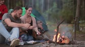 four people : Family rest in the nature with their little son and daughter, they cook marshmallows on open fire and eat them. Stock Footage