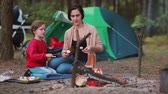 lenha : Happy family having great time together in the nature. Mom teaches her daughter to cook marshmallows on open fire