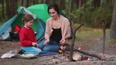 кондитерские изделия : Happy family having great time together in the nature. Mom teaches her daughter to cook marshmallows on open fire. Стоковые видеозаписи