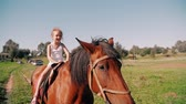 jezdec : A happy little girl riding a horse on a country road on a sunny day. She is smiling, having fun. Slow mo,