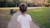 вид : Little girl walking on a road in a park. A bun of fair hair has gold glow in the sun. Slow mo, back view Стоковые видеозаписи