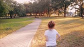 ombro : A cheerful little girl runs on a road in a park on a sunny summer day. Back view, slow mo