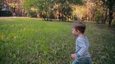 família : A cute little boy happily walking on grass in a park on a sunny summer day. Slow mo